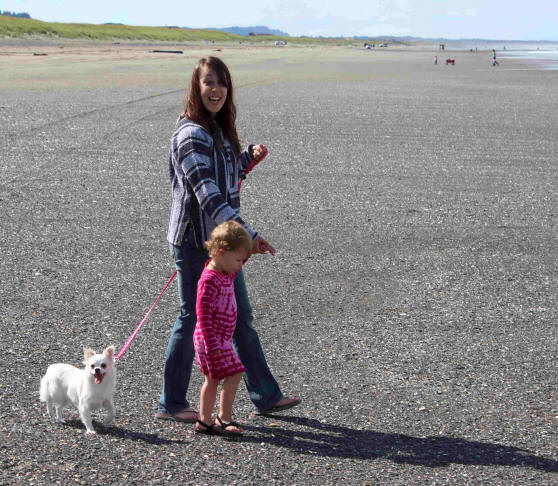 young lady with toddler and dog on leash on beach